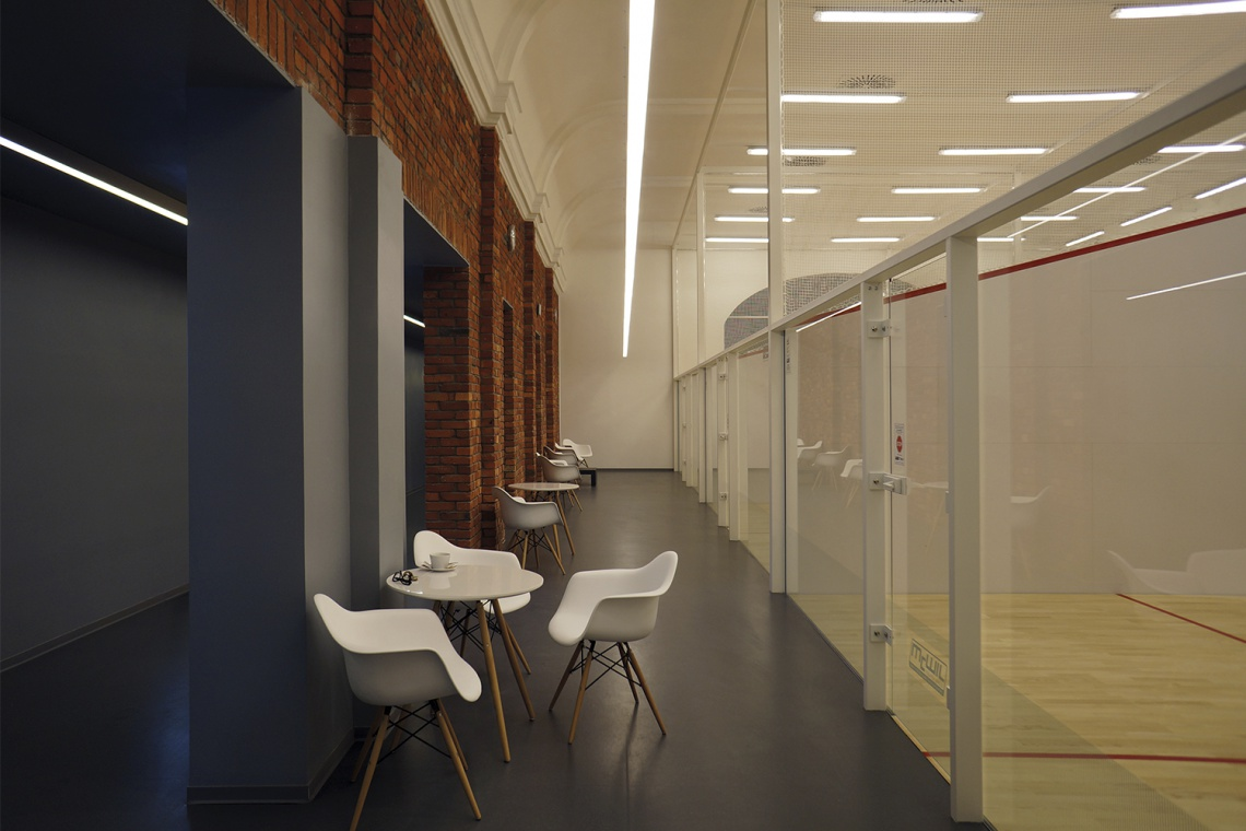 Minimalistyczne i oszczędne w formie wnętrze klubu squashowego