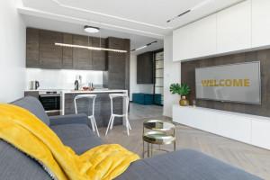Uniwersalny minimalizm, drewno i biel, czyli apartament na wynajem według LOOFT