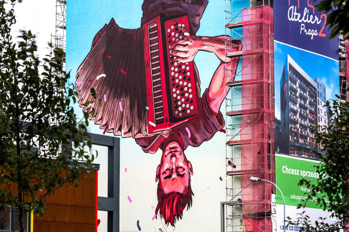 Ten mural przedstawia odwróconego do góry nogami praskiego grajka z akordeonem