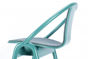 Projektant subtelnie połączył wygięte elementy z litego drewna z wizualnie lekkim siedziskiem